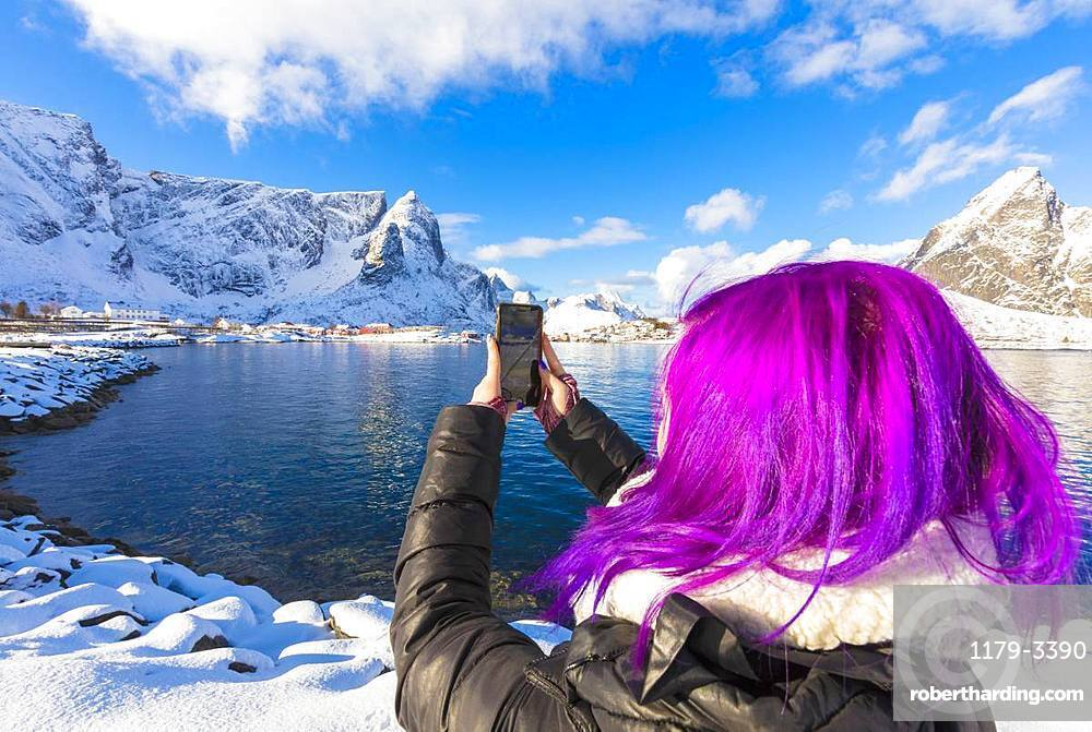 Woman with fuchsia hair taking photo with smartphone, Reine Bay, Lofoten Islands, Nordland, Norway, Europe