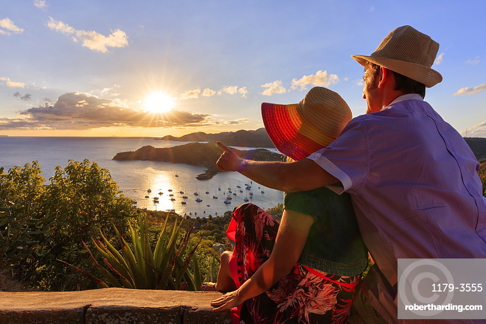 Couple look towards English Harbour from Shirley Heights at sunset, Antigua, Antigua and Barbuda, Leeward Islands, West Indies, Caribbean, Central America