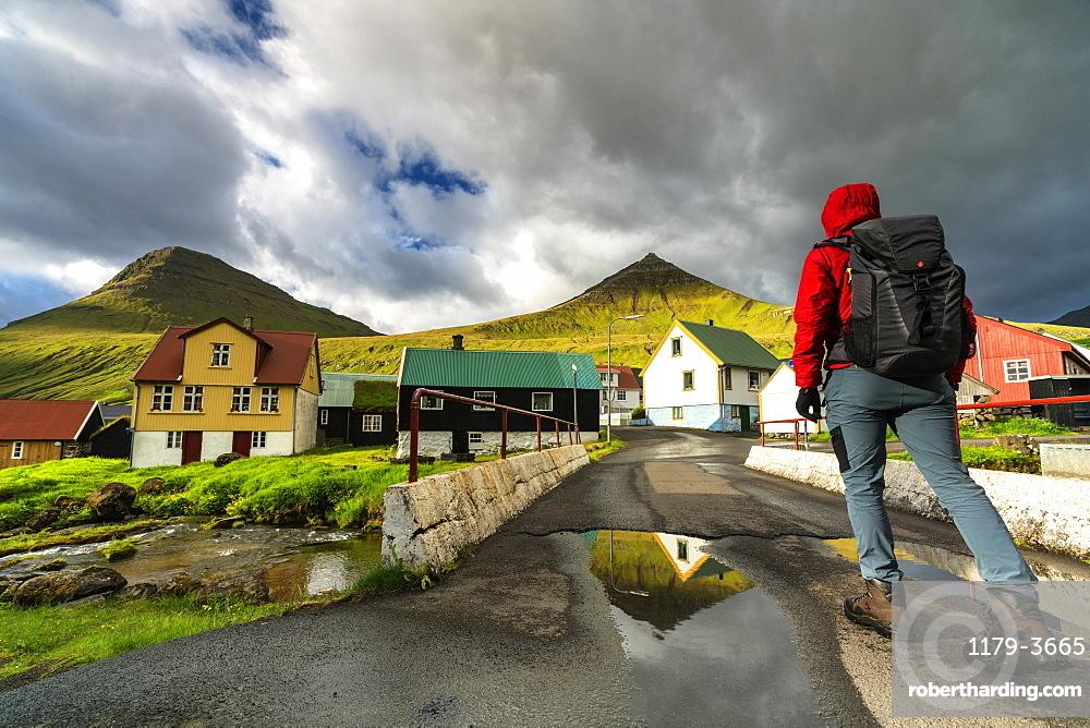 Hiker in the traditional village of Gjogv, Eysturoy island, Faroe Islands, Denmark, Europe