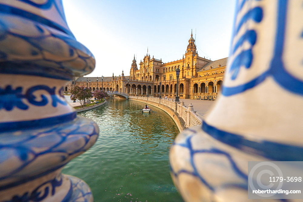 Rowing boat along the canal seen from the ceramic decorated pillars of balustrade, Plaza de Espana, Seville, Andalusia, Spain, Europe