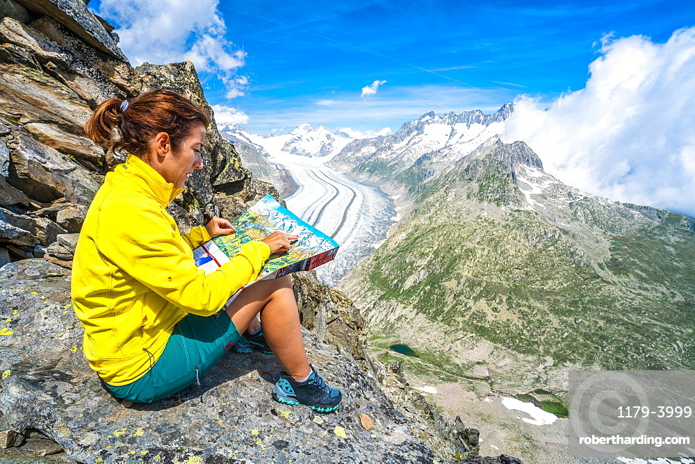 Woman looking at map sitting on rocks at Eggishorn viewpoint above Aletsch Glacier, Bernese Alps, canton of Valais, Switzerland