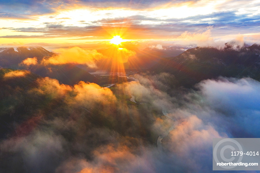 Aerial view of sun rays at sunset lighting up the clouds over Romsdalen valley, Andalsnes, More og Romsdal county, Norway (drone)