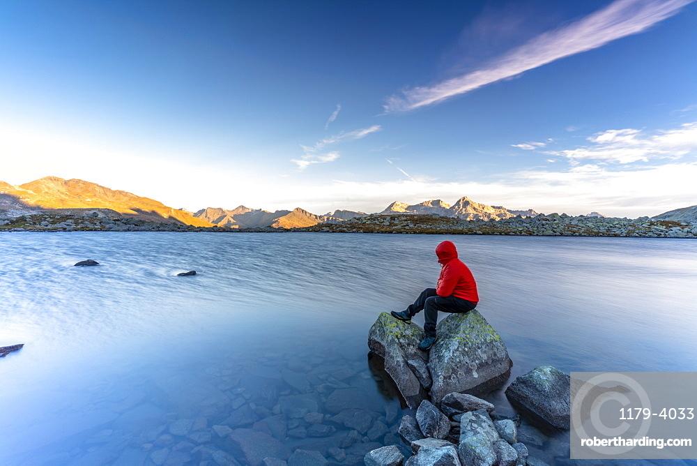 Hiker sitting on rocks on water edge of Laghi Azzurri (Bergsee) at dawn, Spluga Pass, Valle Spluga, Valtellina, Lombardy, Italy, Europe