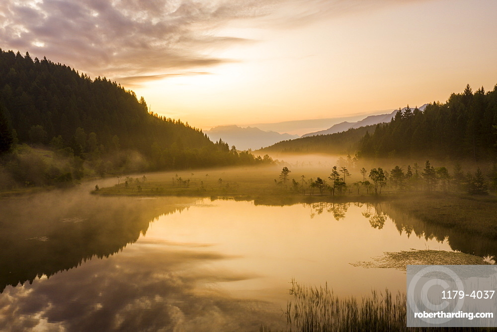 Sky painted orange at dawn with misty land of Pian di Gembro nature Reserve, aerial view, Aprica, Valtellina, Lombardy, Italy, Europe