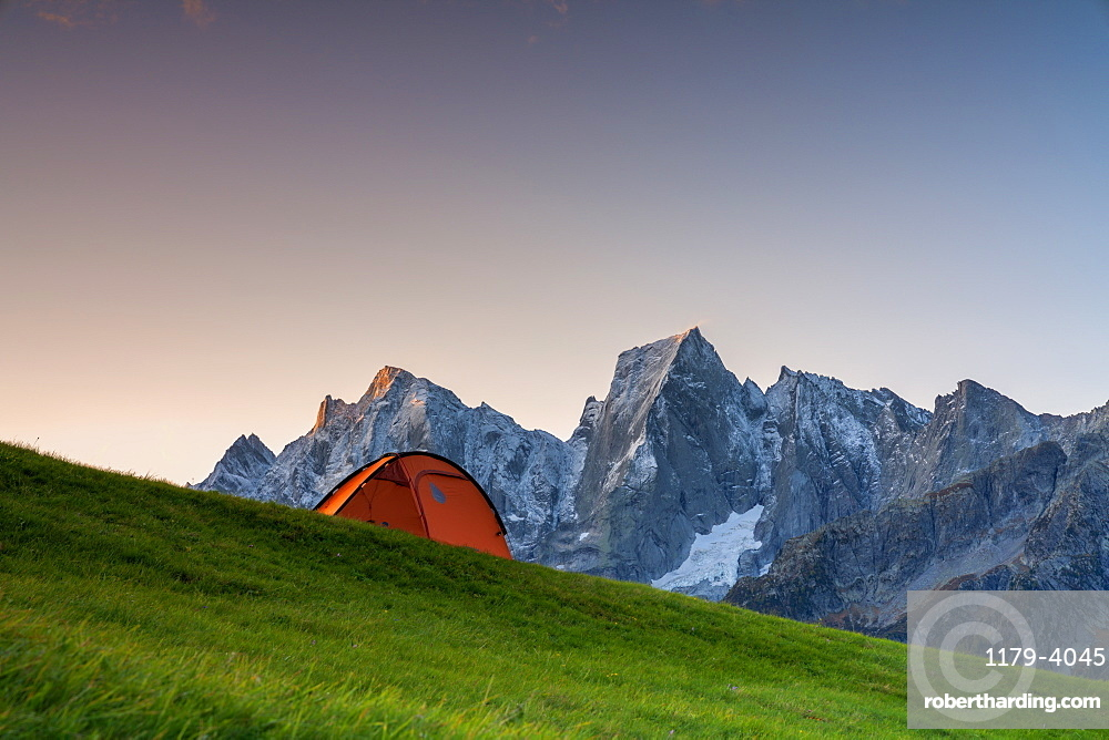 Sunrise lights over a tent overlooking Piz Badile and Cengalo, Tombal, Soglio, Val Bregaglia, canton of Graubunden, Switzerland