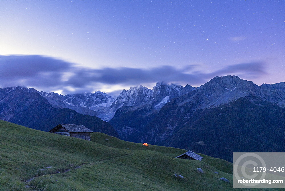 Stars over tent and huts overlooking Piz Badile and Piz Cengalo, Tombal, Soglio, Valbregaglia, canton Graubunden, Switzerland