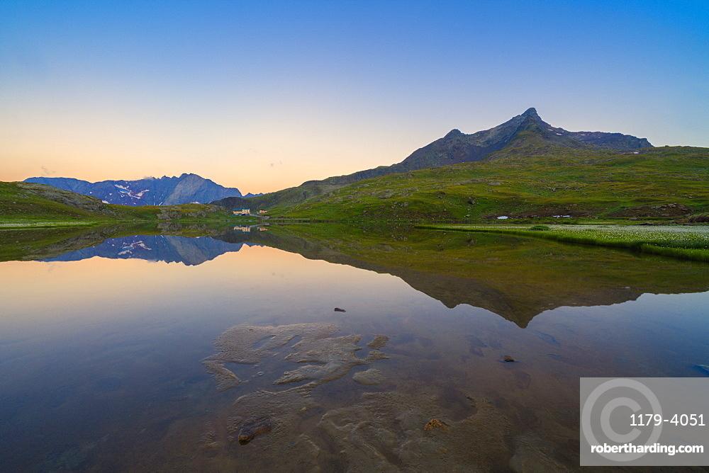 Silhouettes of mountains mirrored in Lago Bianco at dawn, Gavia Pass, Valfurva, Valtellina, Sondrio province, Lombardy, Italy