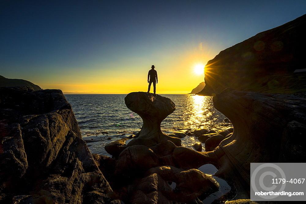 Silhouette of man admiring sunset standing on top of Kannesteinen rock, Oppedal, Vagsoy, Sogn og Fjordane county, Norway