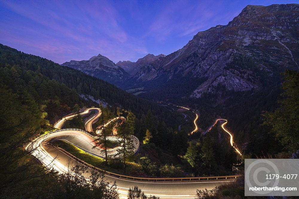 Car trails lights on narrow bends of Maloja Pass mountain road, Engadine, Canton of Graubunden, Switzerland, Europe