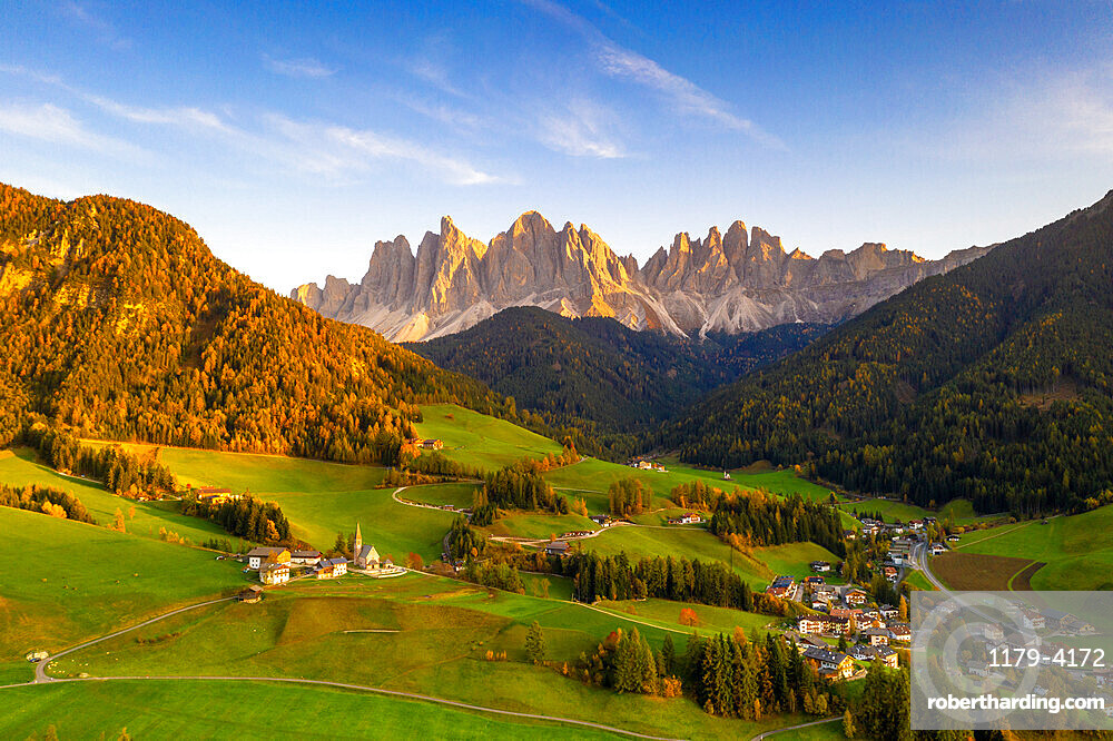 Sunset on the little village of Santa Magdalena and Odle peaks in autumn, aerial view, Funes, Dolomites, South Tyrol, Italy, Europe