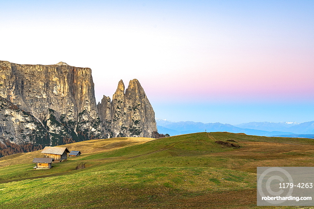Autumn sunrise over Sciliar peaks and wood huts at Alpe di Siusi/Seiser Alm, Dolomites, South Tyrol, Italy