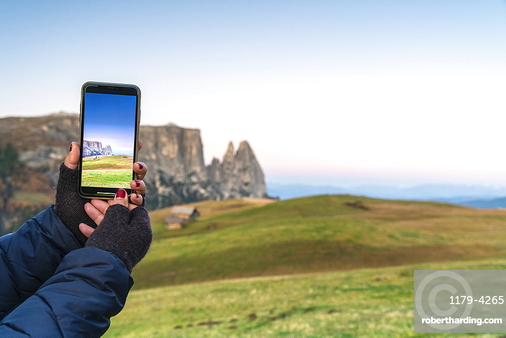 Personal perspective of woman photographing Sciliar peaks with smartphone, Alpe Siusi/Seiser Alm, Dolomites, South Tyrol, Italy