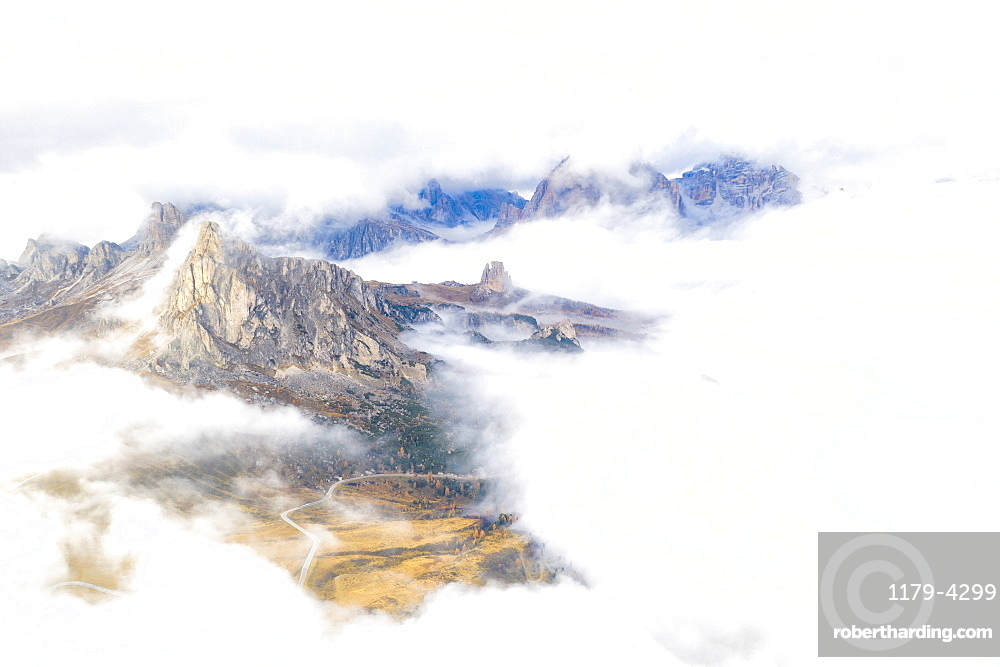 Aerial view by drone of Ra Gusela and Cinque Torri mountains covered by clouds and fog in autumn, Giau Pass, Dolomites, Belluno, Veneto, Italy, Europe