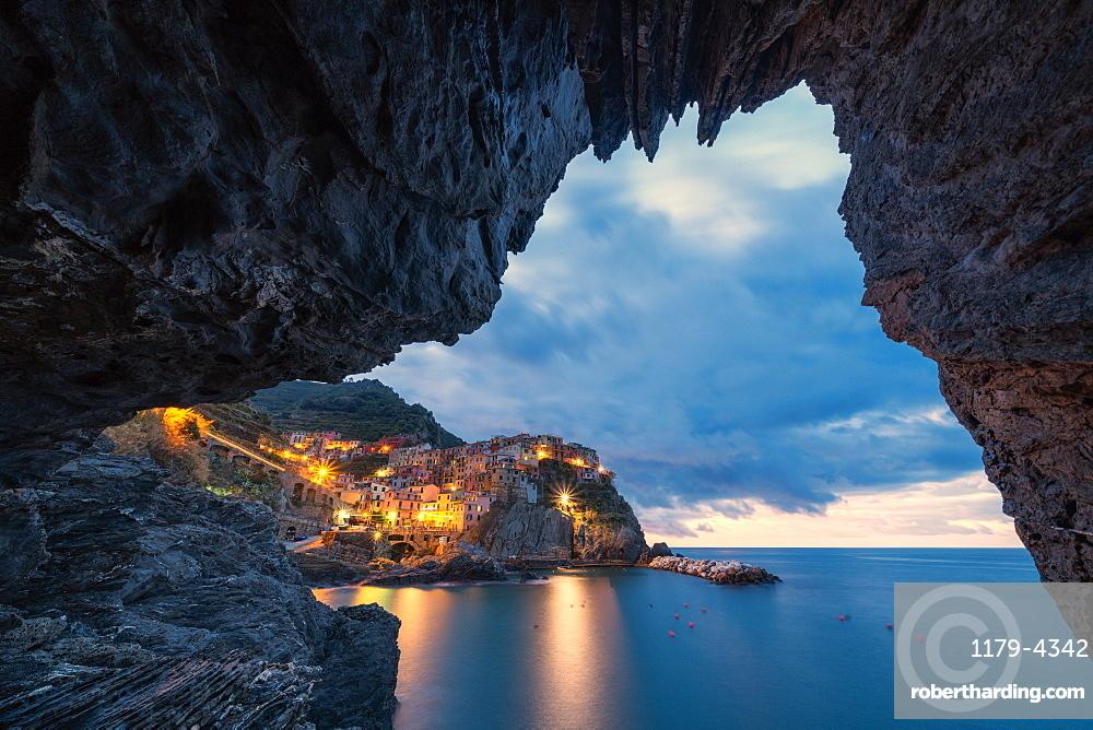Manarola at dusk view from a grotto, Cinque Terre, La Spezia province, Liguria, Italy