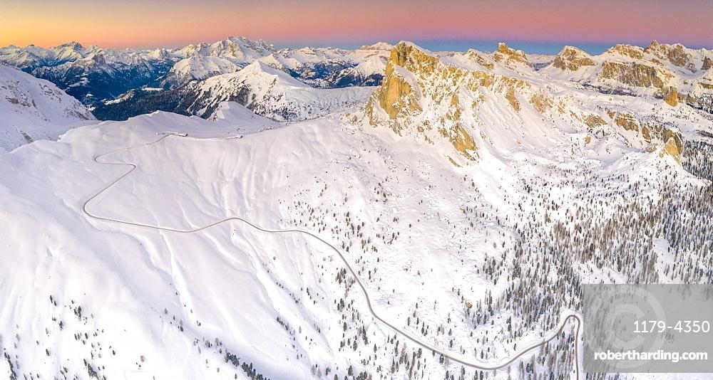 Panoramic of the snowy Giau Pass, Marmolada, Ra Gusela, Nuvolau, Averau and Lagazuoi at dawn, Dolomites, Veneto, Italy (drone)