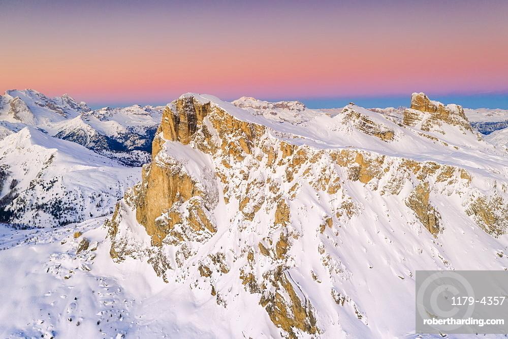 Pink sky at sunrise on Ra Gusela, Nuvolau, Averau, Marmolada covered with snow, Dolomites, Belluno, Veneto, Italy (drone)