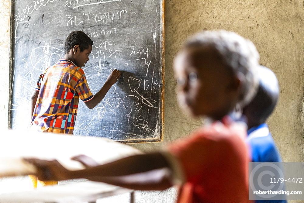 Young boy writing on blackboard at school, Melabday, Asso Bhole, Danakil Depression, Afar Region, Ethiopia, Africa