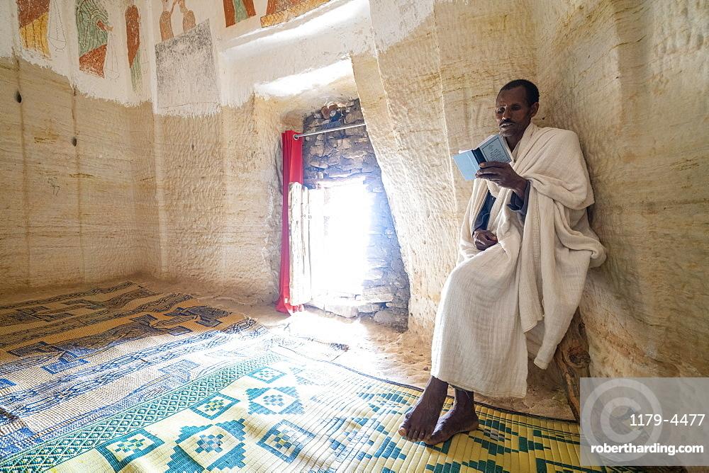 Priest holding the prayer book in the Orthodox Christian Daniel Korkor church, Gheralta Mountains, Tigray Region, Ethiopia