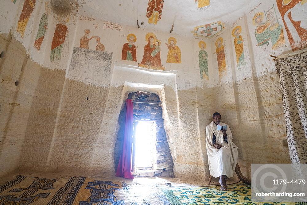 Orthodox Christian priest holding the prayer book inside Daniel Korkor church, Gheralta Mountains, Tigray Region, Ethiopia