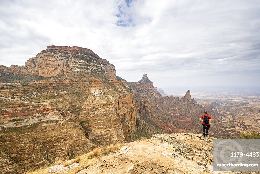 Male hiker admiring Gheralta Mountains canyons from top of rocks, Tigray Region, Ethiopia, Africa