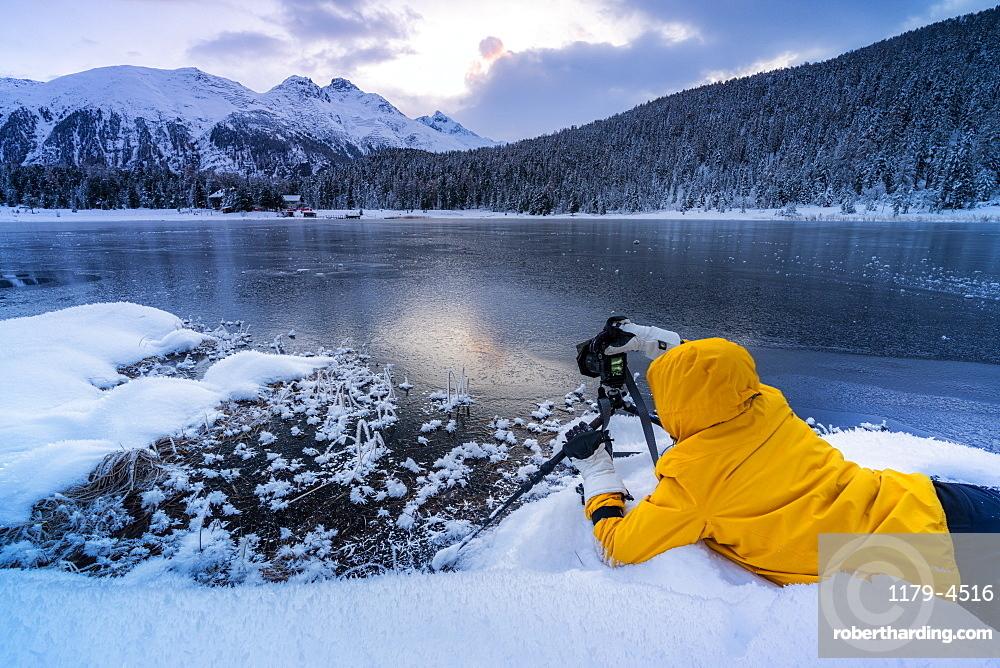 Photographer taking pictures of frozen Lej da Staz at dawn lying on the snow, canton of Graubunden, Engadine, Switzerland