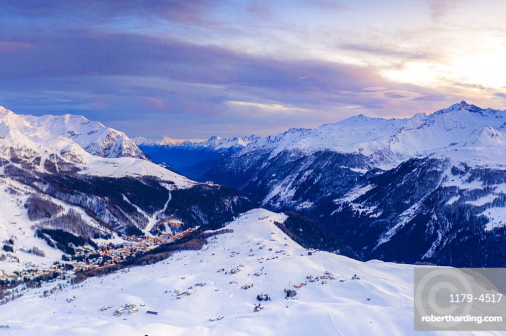 Aerial view of sunset on the snowy peaks surrounding Madesimo and Andossi, Valchiavenna, Valtellina, Lombardy, Italy (drone)