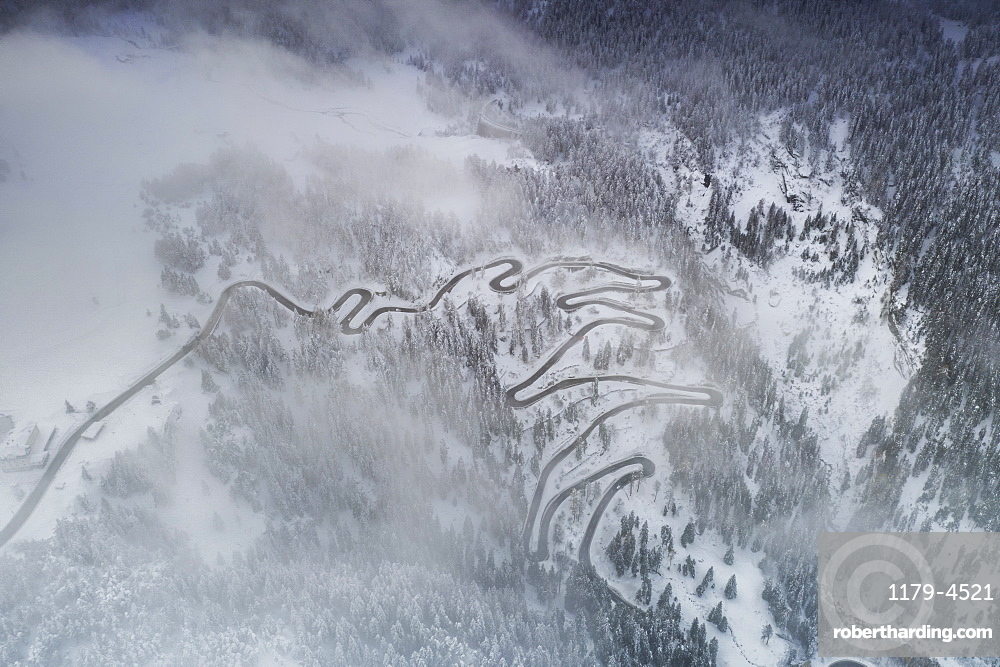 Fog on bends of Maloja Pass road and snowy woods, aerial view, Bregaglia Valley, canton of Graubunden, Engadine, Switzerland
