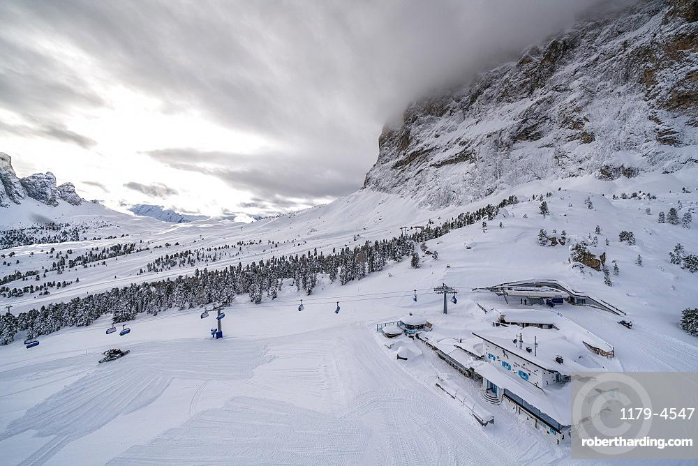 Clouds over the snowy slopes of Sella Pass ski area, Val Gardena, Dolomites, Trentino-Alto Adige, Italy