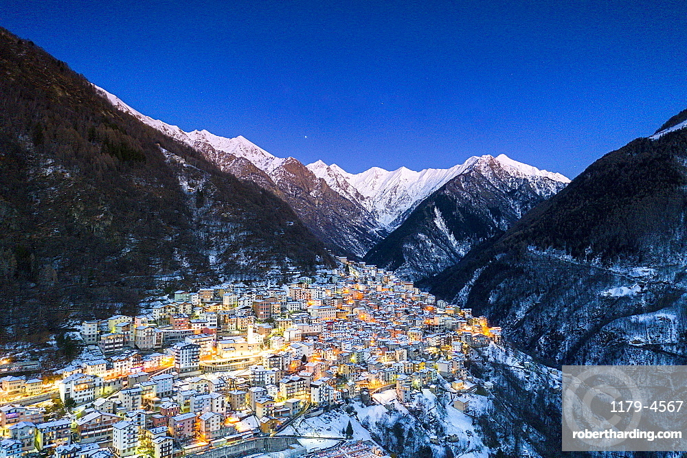 Winter dusk over the illuminated village of Premana, aerial view, Valsassina, Lecco province, Lombardy, Italy (drone)