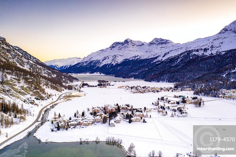 Snowy village of Segl (Sils im Engadin) on shores of Lake Sils at dawn, Engadin, canton of Graubunden, Switzerland