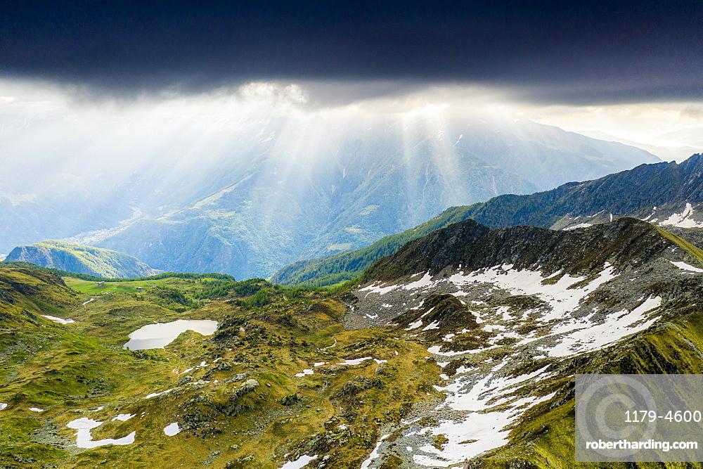 Light beam at sunrise over mountains peaks surrounding Arcoglio lake, Valmalenco, Sondrio province, Valtellina, Lombardy, Italy