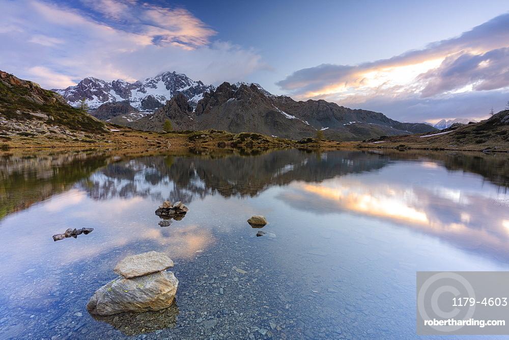 Sunrise lit the rocky peak of Monte Disgrazia mirrored in the clear water of lake Zana, Valmalenco, Valtellina, Lombardy, Italy
