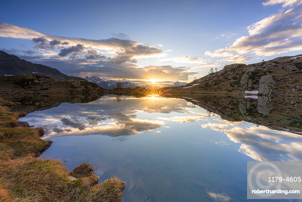 Sunburst over the clear waters of lake Zana during sunrise, Valmalenco, Sondrio province, Valtellina, Lombardy, Italy