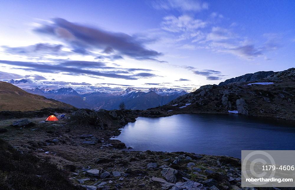 Tent of hikers on shores of the alpine lake Zana during sunrise, Valmalenco, Sondrio province, Valtellina, Lombardy, Italy