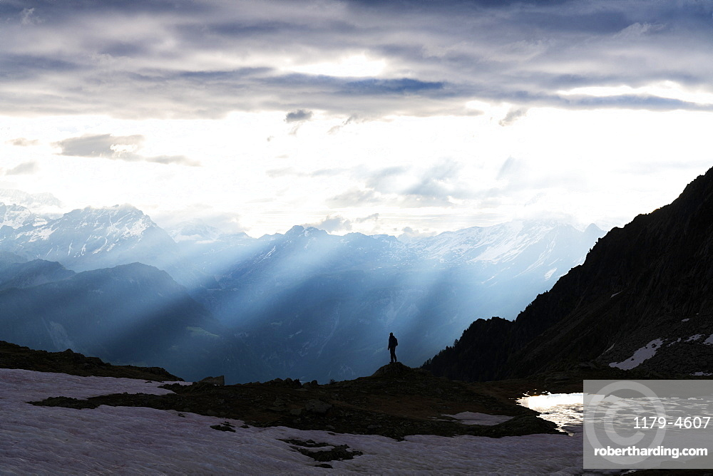 Silhouette of lone hiker admiring the sun rays at dawn over lake Zana, Valmalenco, Valtellina, Lombardy, Italy
