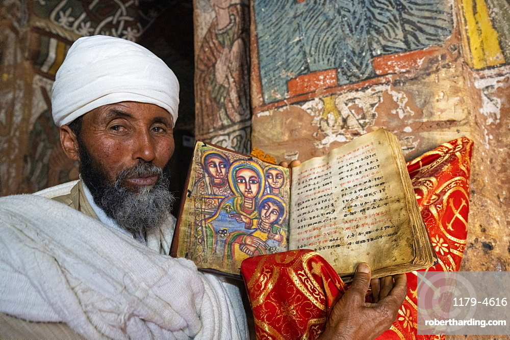 Orthodox priest holding a old bible with hand-painted saints, Abuna Yemata Guh church, Gheralta Mountains,Tigray Region, Ethiopia