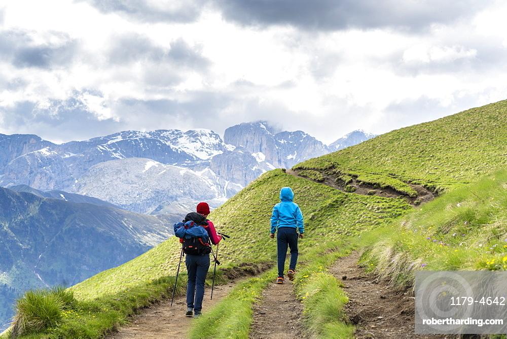 Rear view of mother with male child trekking around the Sassolungo group, Dolomites, Trentino-Alto Adige, Italy, Europe