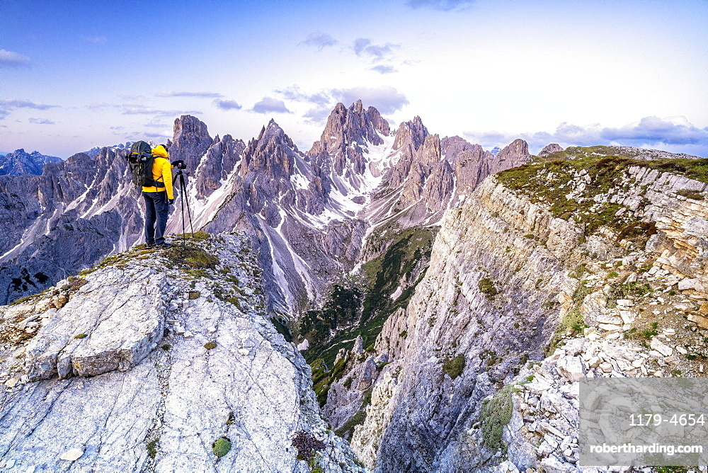 Man on top of rocks photographing Cadini di Misurina at sunrise, Dolomites, Belluno province, Veneto, Italy, Europe