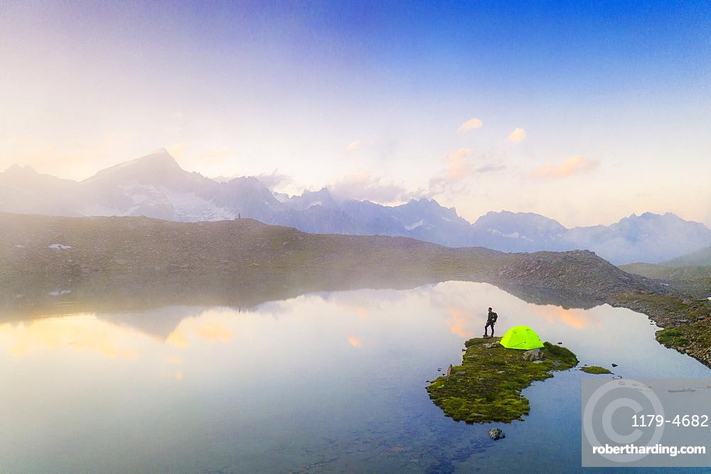 Hiker man with tent admiring a misty sunrise over mountains from Obere Schwarziseeli lake, Furka Pass, Canton Uri, Switzerland, Europe
