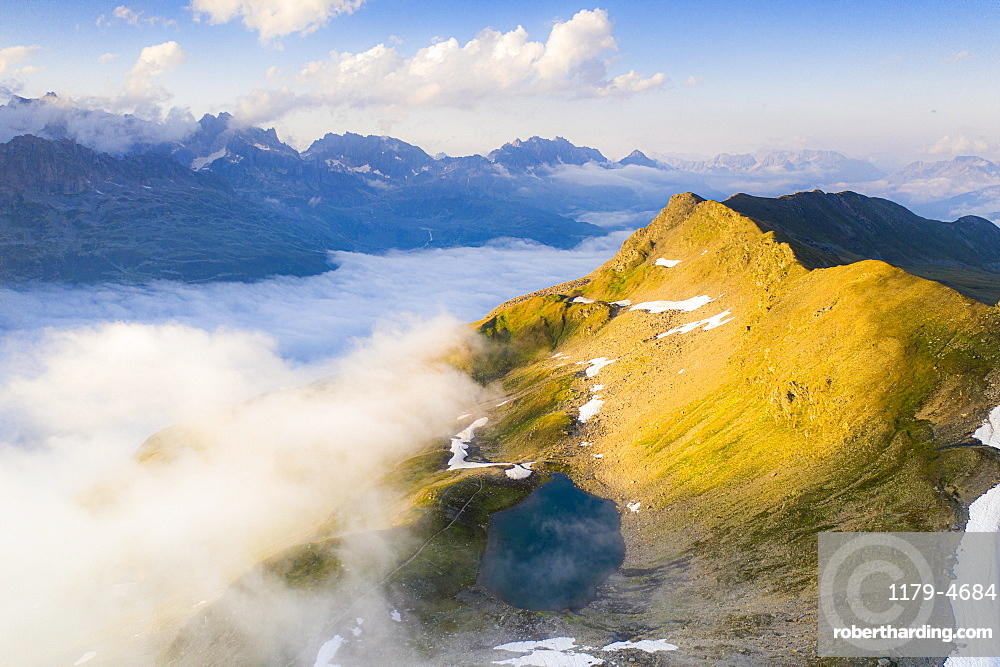 Schwarziseeli lake and Stotzigen Firsten mountain emerging from a sea of clouds, aerial view, Furka Pass, Canton Uri, Switzerland, Europe