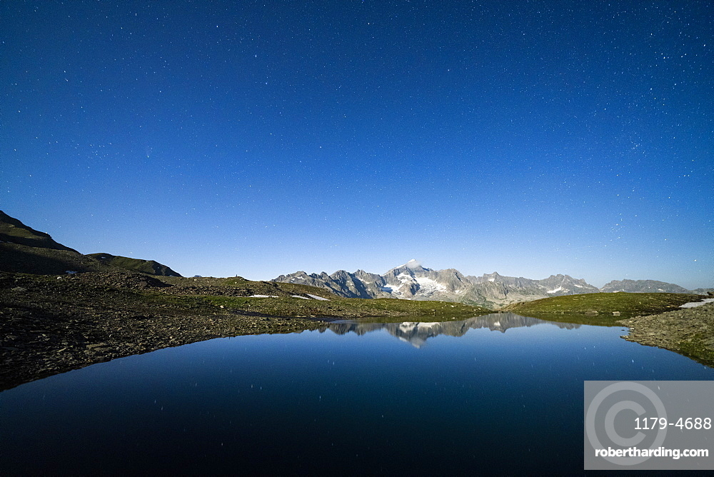 Starry sky over Galenstock mountain reflected in the pristine Mittleres Schwarziseeli lake, Furka Pass, Canton Uri, Switzerland, Europe