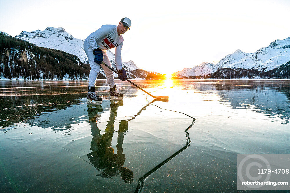 Front view of ice hockey player on cracked surface of frozen Lake Sils, canton of Graubunden, Engadine, Switzerland