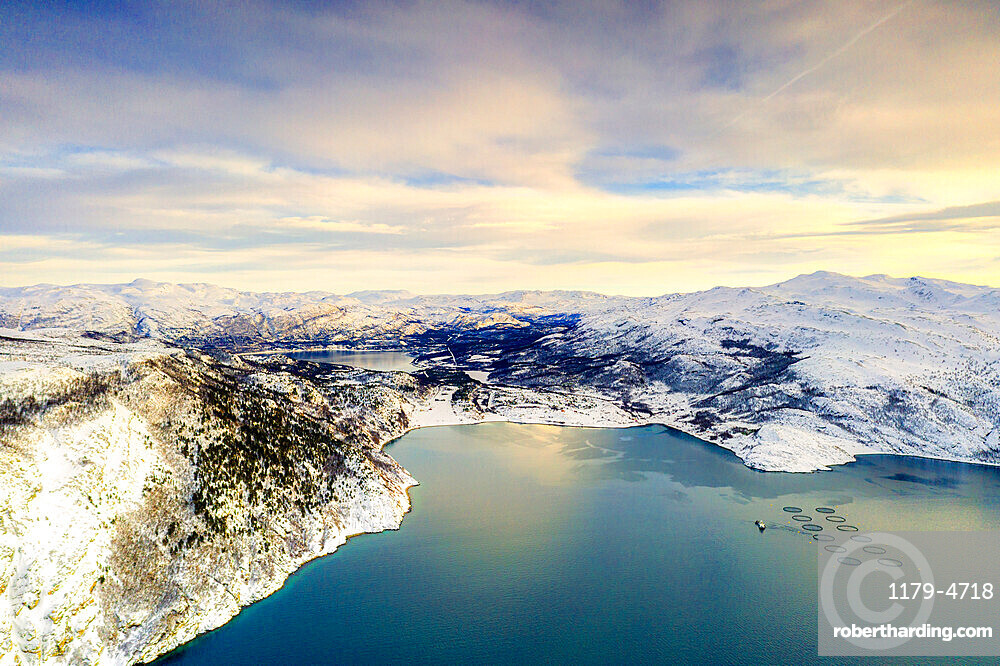 Aerial view of cloudy sky at sunset over fish farms and mountains along Altafjord in winter, Troms og Finnmark, Northern Norway, Scandinavia, Europe
