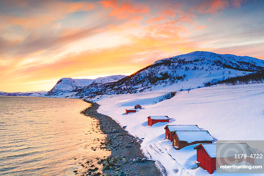 Sunset over red cabins in the snow along Porsangerfjord with North Cape (Nordkapp) on background, Troms og Finnmark, Norway