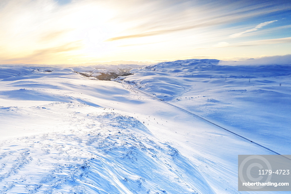Empty road across mountains covered with snow lit by sunrise, aerial view, Sennalandet, Alta, Troms og Finnmark, Norway
