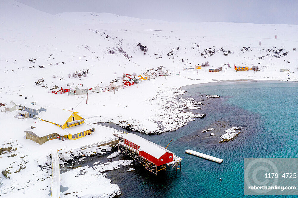 Fishing village of Sorvaer framed by the cold sea during a snowy winter, Soroya Island, Hasvik, Troms og Finnmark, Norway