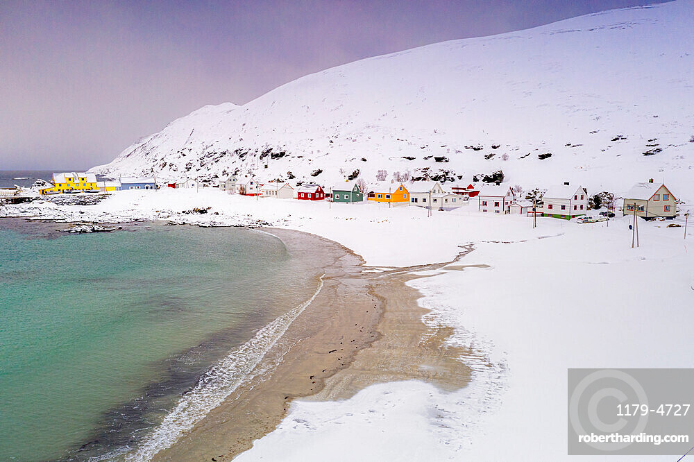 Cold sea surrounding Sorvaer village and sand beach covered with snow, Soroya Island, Hasvik, Troms og Finnmark, Norway