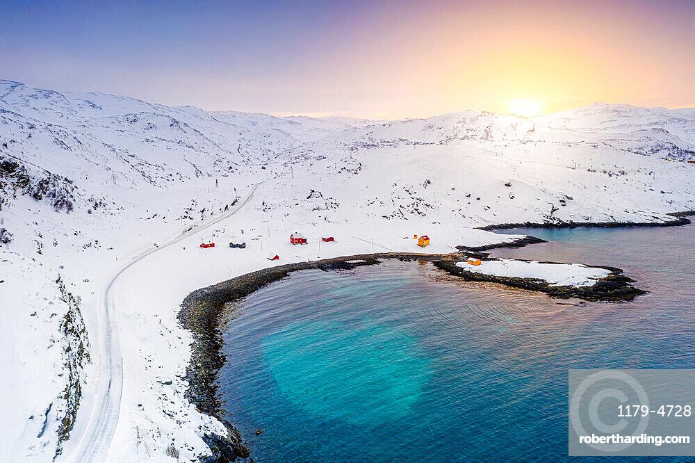 Snowy road towards the fishing village of Breivikbotn at sunset, Soroya Island, Hasvik, Troms og Finnmark, Northern Norway