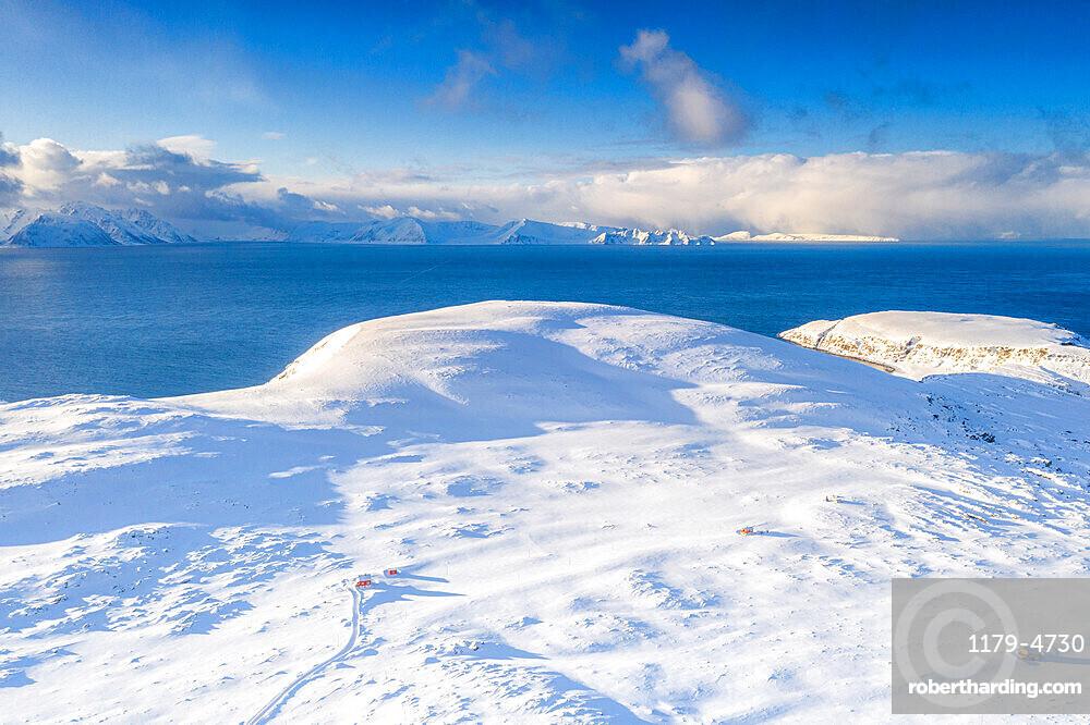 Aerial view of white mountains covered with snow surrounding the blue frozen sea, Hasvik, Soroya Island, Troms og Finnmark, Arctic, Norway, Scandinavia, Europe