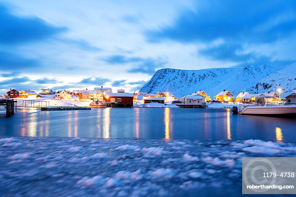 Winter dusk over the frozen sea surrounding the fishing village of Sorvaer, Soroya Island, Troms og Finnmark, Northern Norway, Scandinavia, Europe